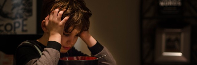 Picture is a boy sitting at a kitchen table staring into his cereal bowl.
