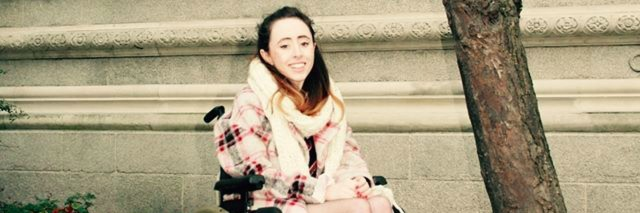 Niamh Herbert in a wheelchair outside.