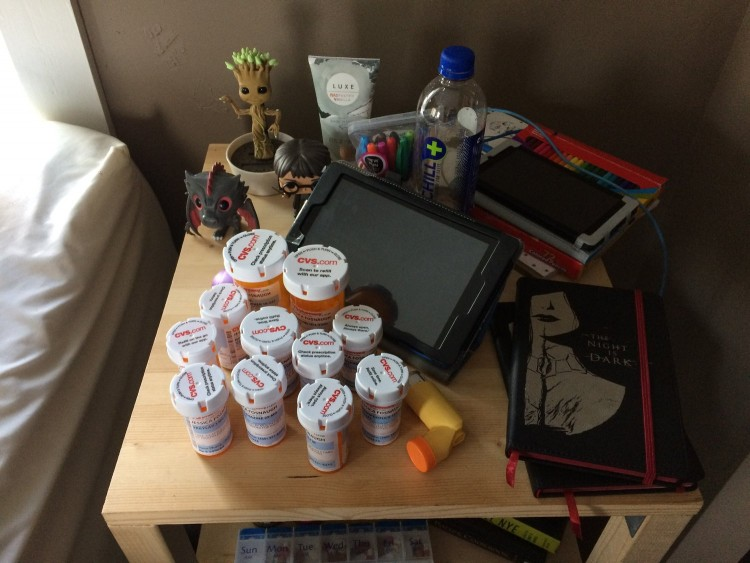 Nightstand with a bunch of pill bottles on it.