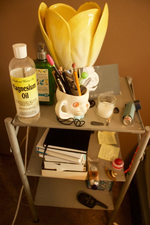 Emma Jones' nightstand featuring magnesium oil and a tulip lamp.