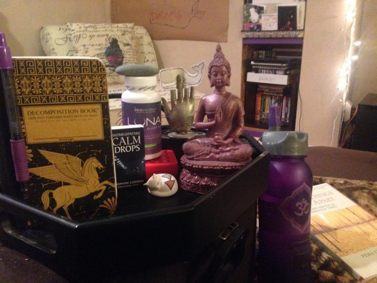 Nightstand with a purple buddha statue, calm drops and a notebook.