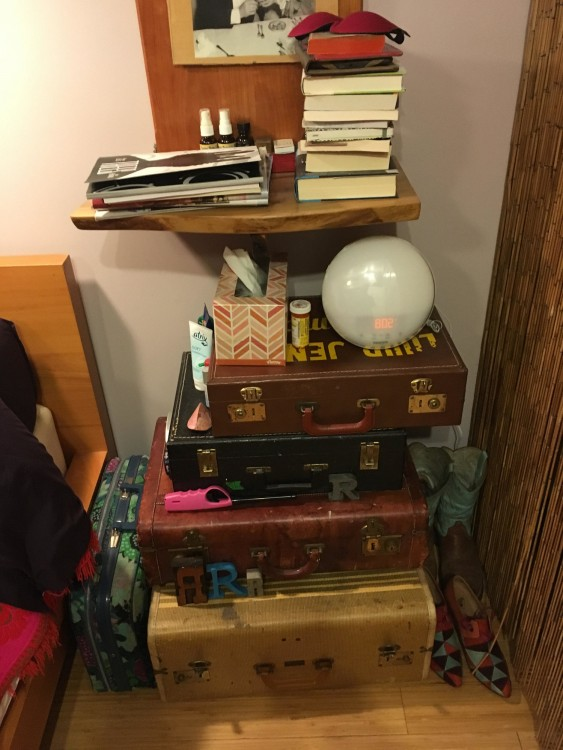 Nightstand made of suitcases with a bunch of books on top and a spherical alarm clock.