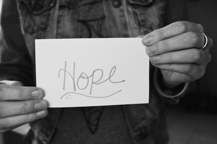 black and white photo of woman holding a note card that says 'hope'