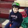 Boy wearing hoodie and dinosaur-themed bike helmet