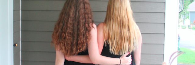 two girls with their arms around each other, back view
