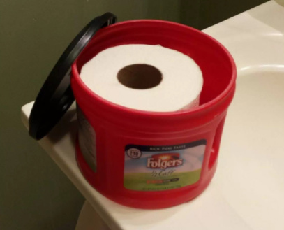 plastic Folgers coffee canister filled with toilet paper roll