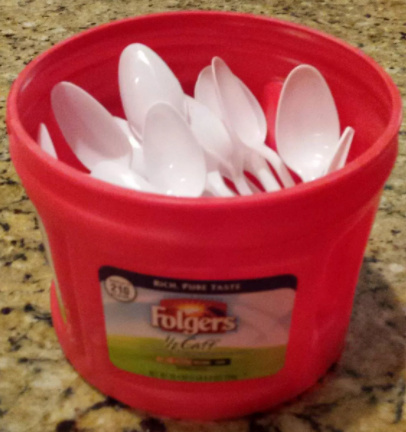 plastic Folgers coffee can filled with plastic spoons