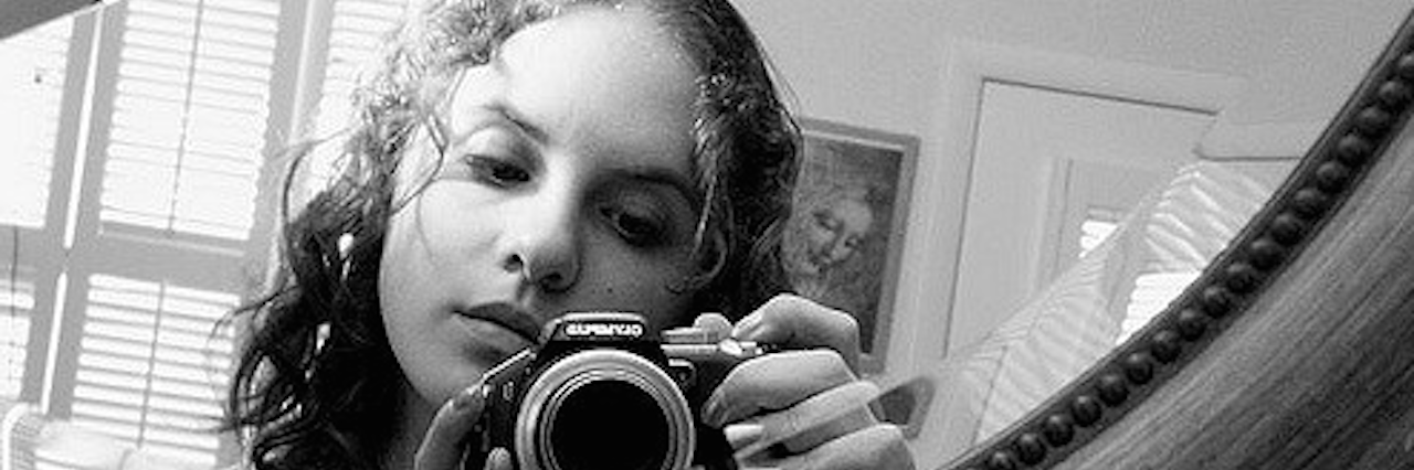 woman holding camera up to mirror