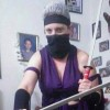 The author dressed up for Halloween as a video game character, holding two swords with the lower half of her face and her forehead covered by black fabric