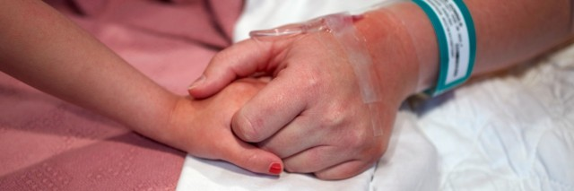 Female hospital patient holding a preschool age girl's hand.
