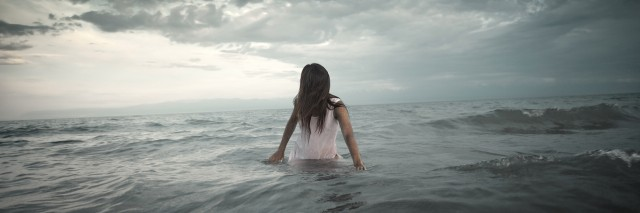 A woman standing in a stormy ocean