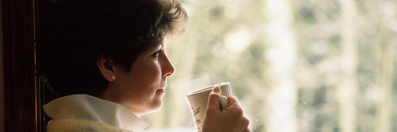 woman drinking tea by window