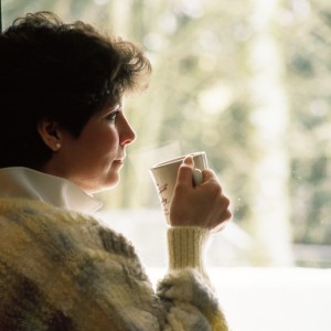 woman drinking tea by window