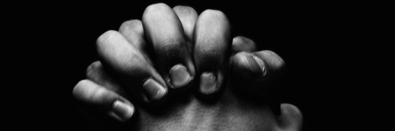 man holding his hands together in prayer