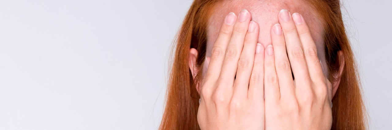 woman with long red hair covers her face with her hands
