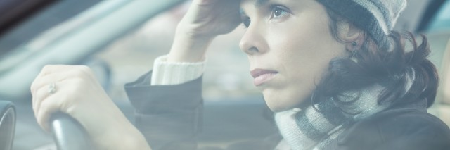 Mid adult looking away with sad expression while driving her car