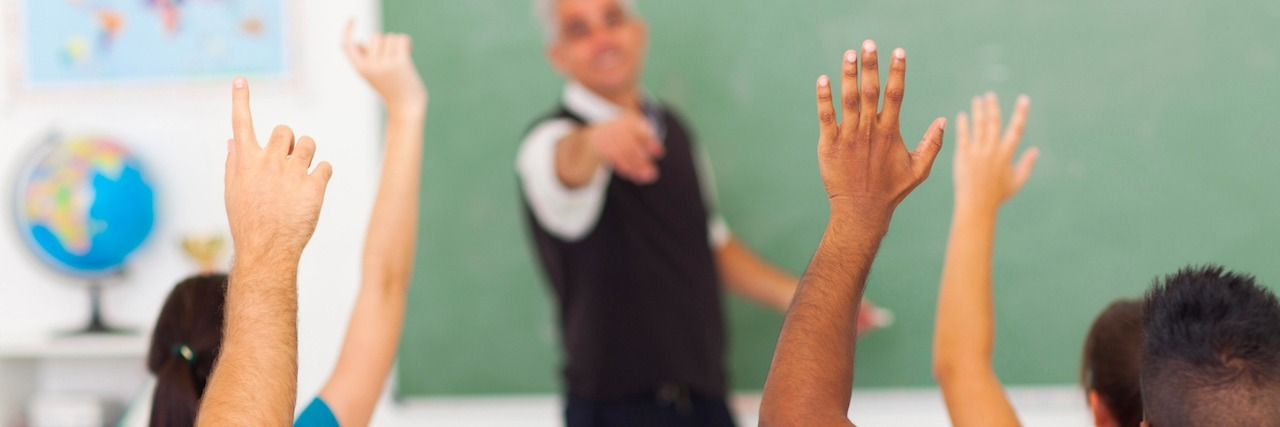 high school students with hands up in classroom with teacher pointing to student