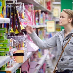 Woman in gray sweatshirt shopping for toys