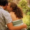 couple sitting outdoors, woman kissing man, rear view