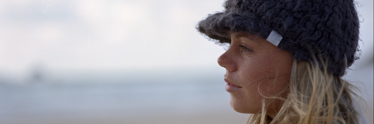 Young woman wearing hat, standing on beach, profile