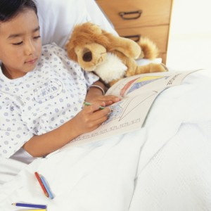 Boy lying in hospital bed with toy animal, drawing in book