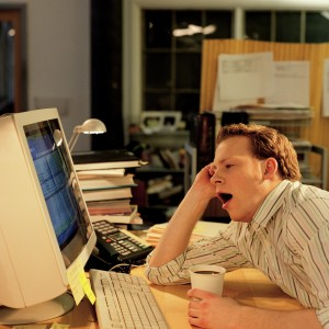 Man sitting in front of a computer, yawning