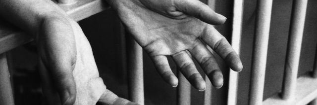 hands in a jail cell