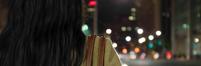 Woman standing at a street intersection at night with out of focus lights