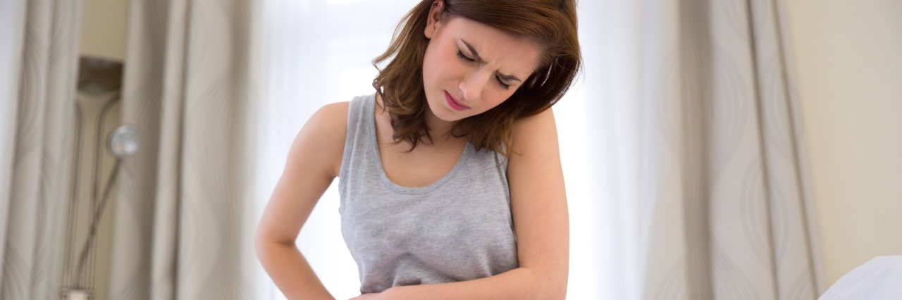 Young woman sitting on the bed with pain in stomach