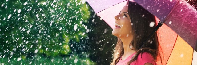 woman holds colorful umbrella in the rain and laughs