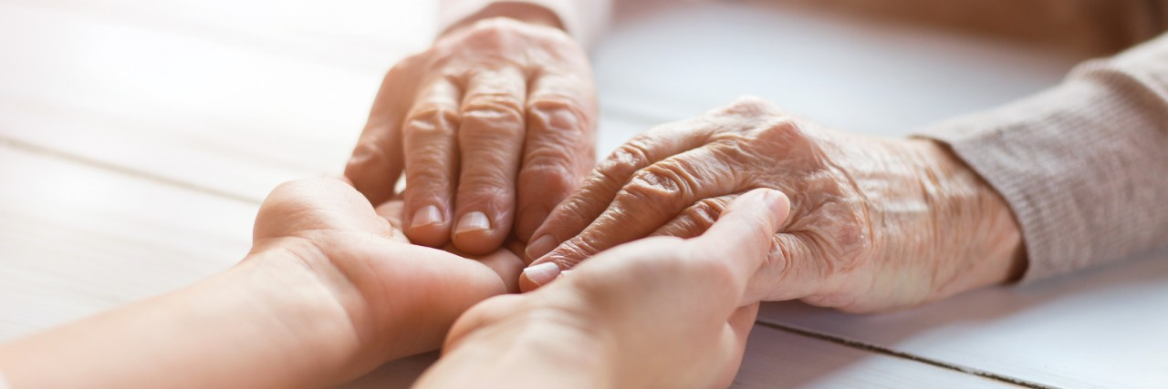 Up close photo of a senior woman's hands being held