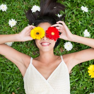 woman in white dress laying on the grass and holding red and yellow flowers over her eyes