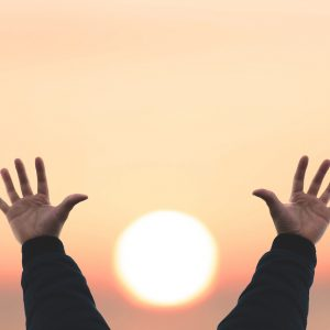A man reaching his hand out in the sky