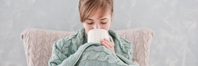woman wrapped in blanket and drinking out of mug