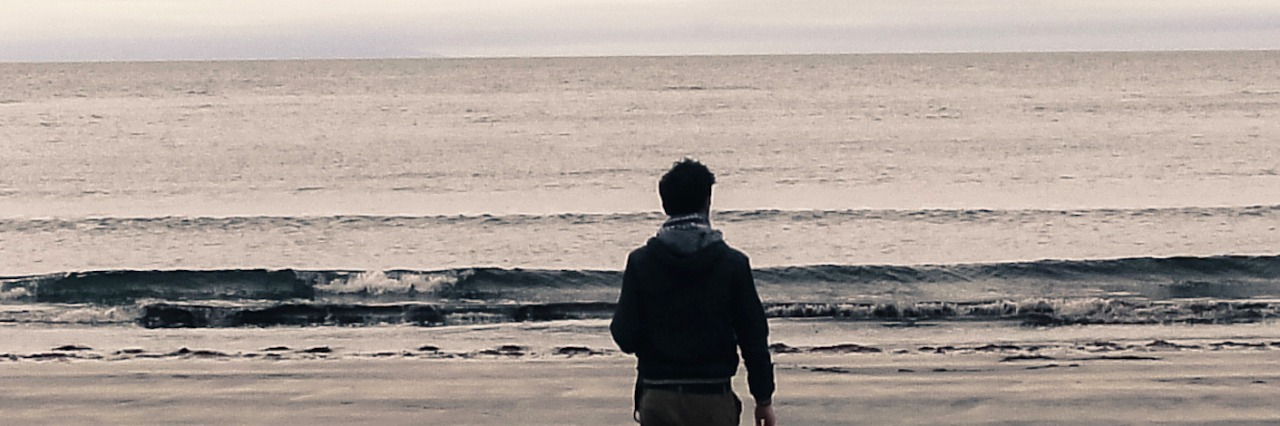 Picture of man from behind walking on a beach on an overcast day