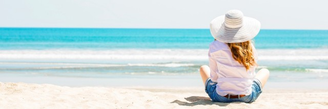 young woman sitting on the beach in white hat at sunny day