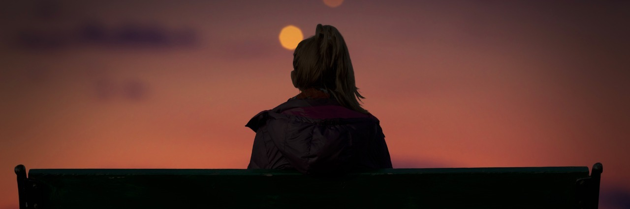 silhouette of a girl watching defocused city lights