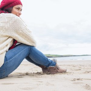 woman in sweater and jeans sitting on the beach and hugging her knees
