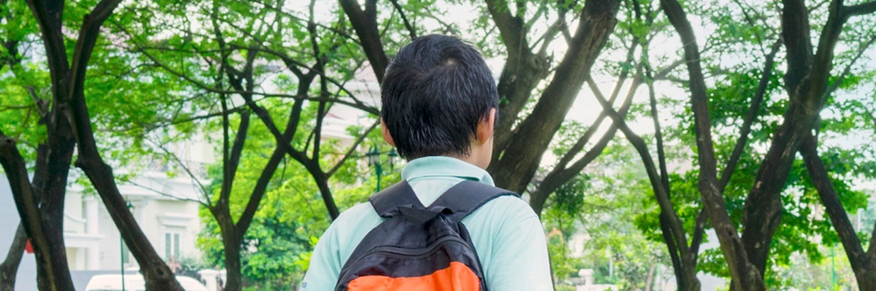 Boy wearing backpack, walking near grass and trees