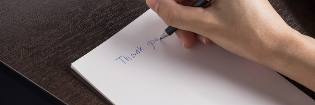 A woman writing a thank you letter