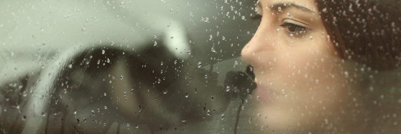 Sad woman looking through a car window