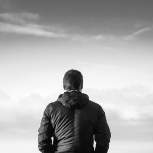 Black and white photo of man in front of gray sky