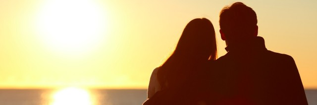 Back view of a couple silhouette hugging and watching sun on the beach