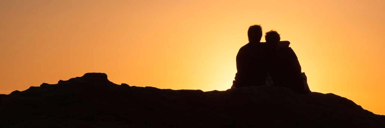 Silhouette of two people sitting on a rock at sunset