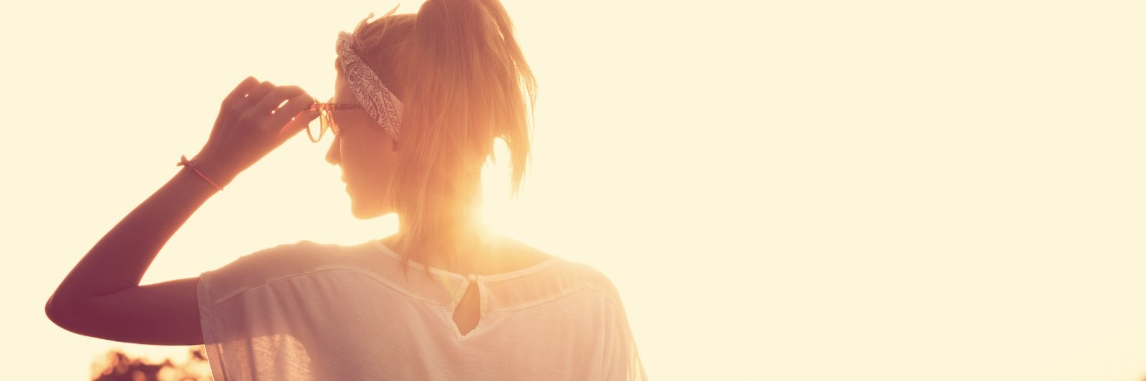 woman in white shirt adjusting her glasses and looking at the sun