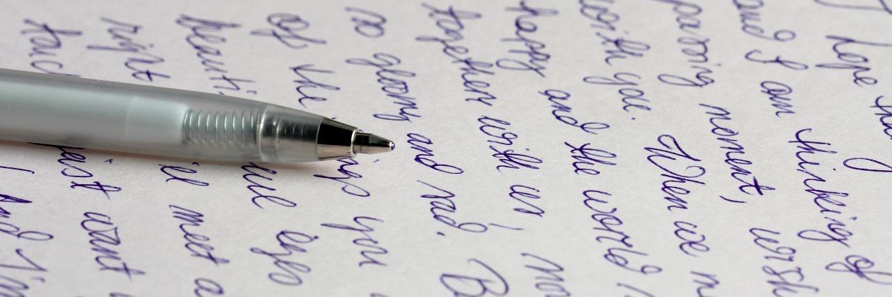 A handwritten letter with a silver ballpoint pen.