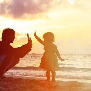 Father and little daughter playing silhouettes on beach at sunset