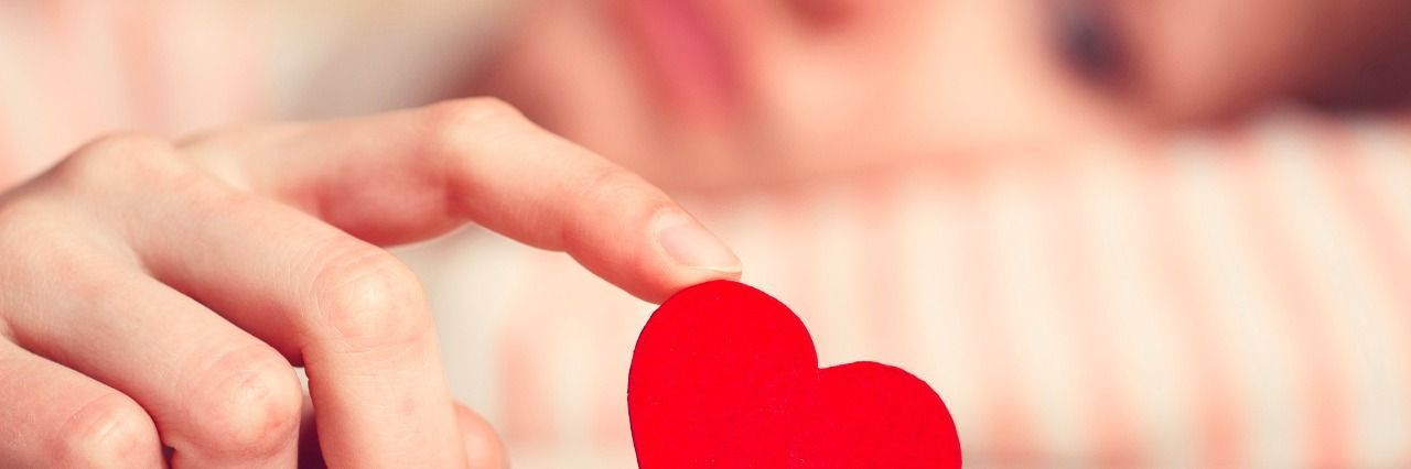 girl is holding heart symbol by her finger and looking at it
