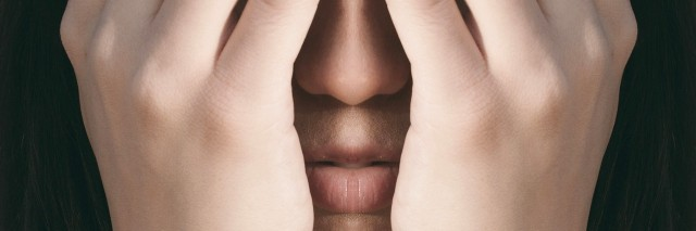 Mirrored photograph of a woman hiding here face