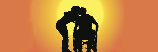 Silhouette of a male and female couple at sunset. The man uses a wheelchair.